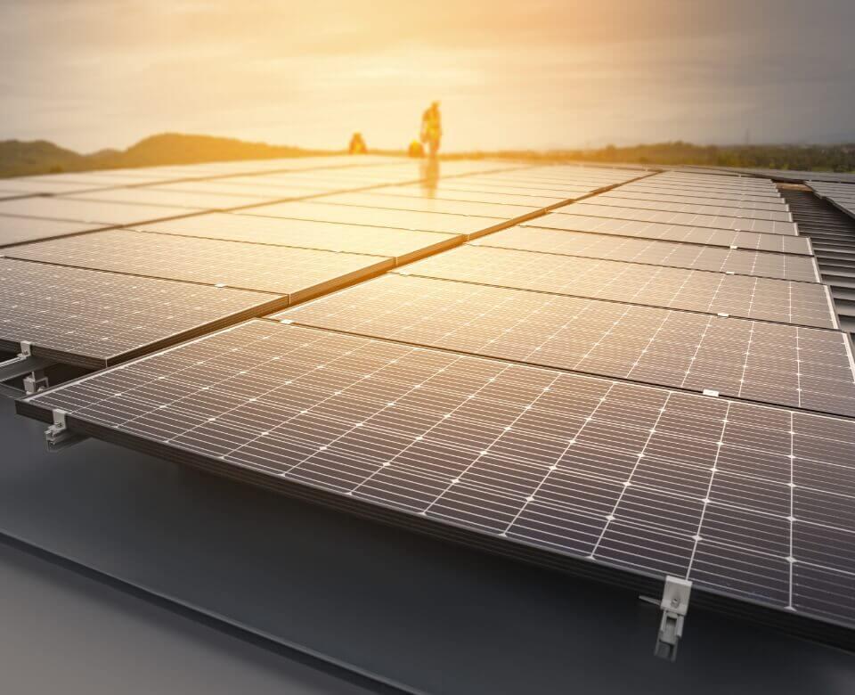 sun setting behind solar panels