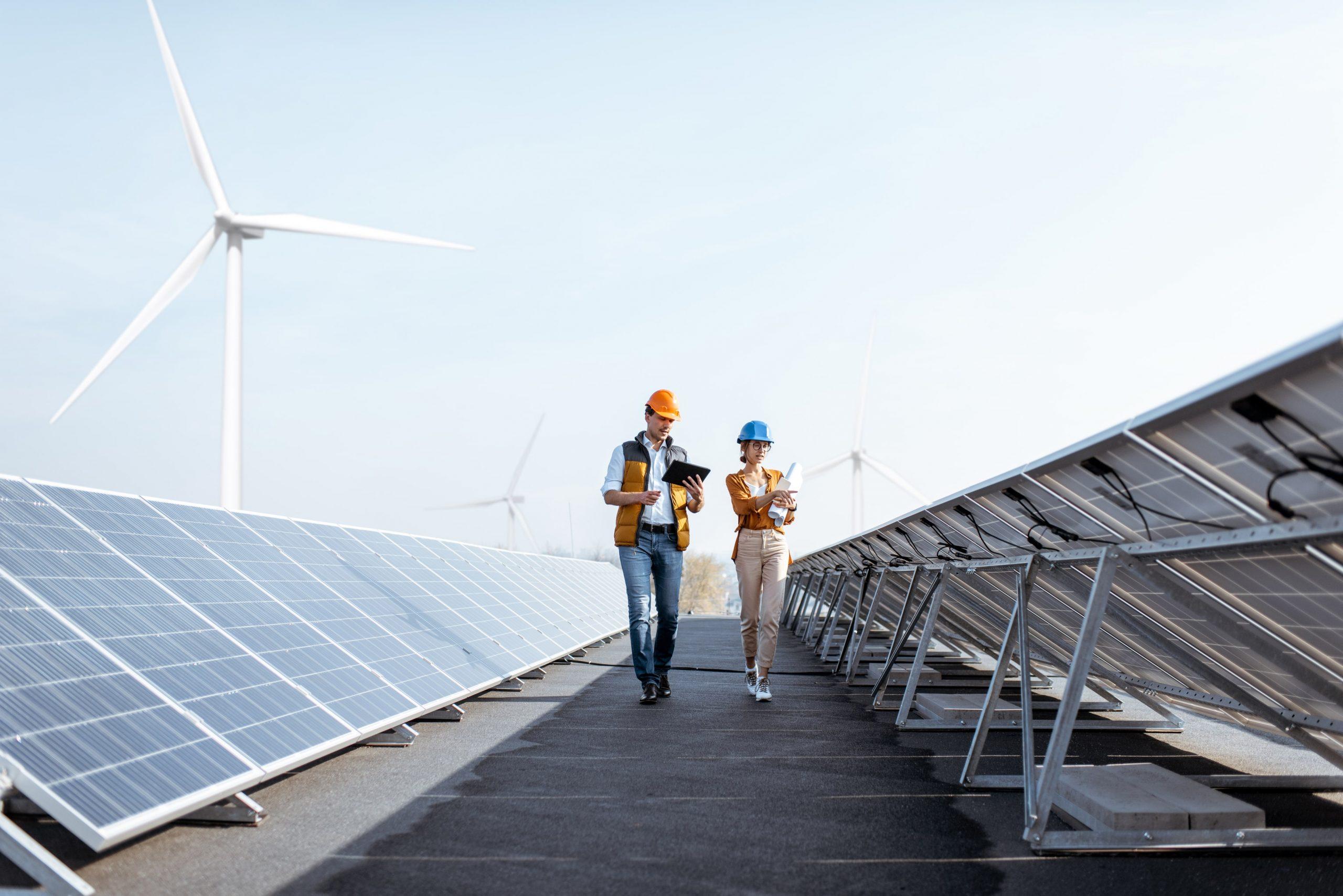 two workers walking between solar panels