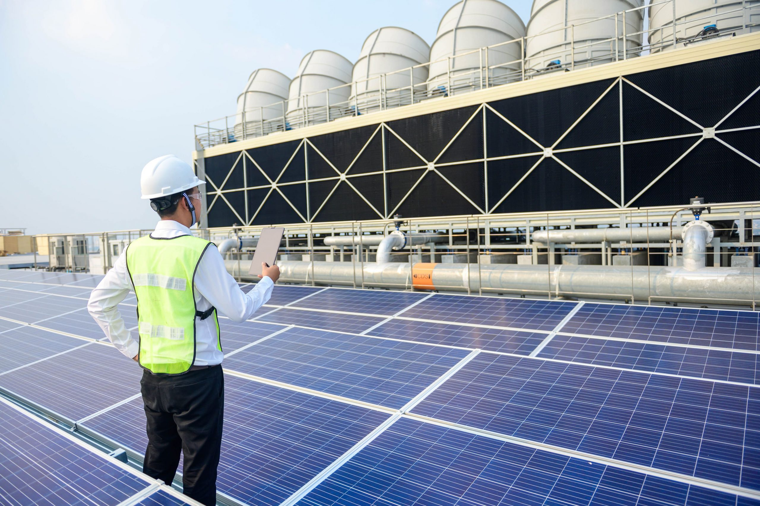 man standing between solar panels on a roof