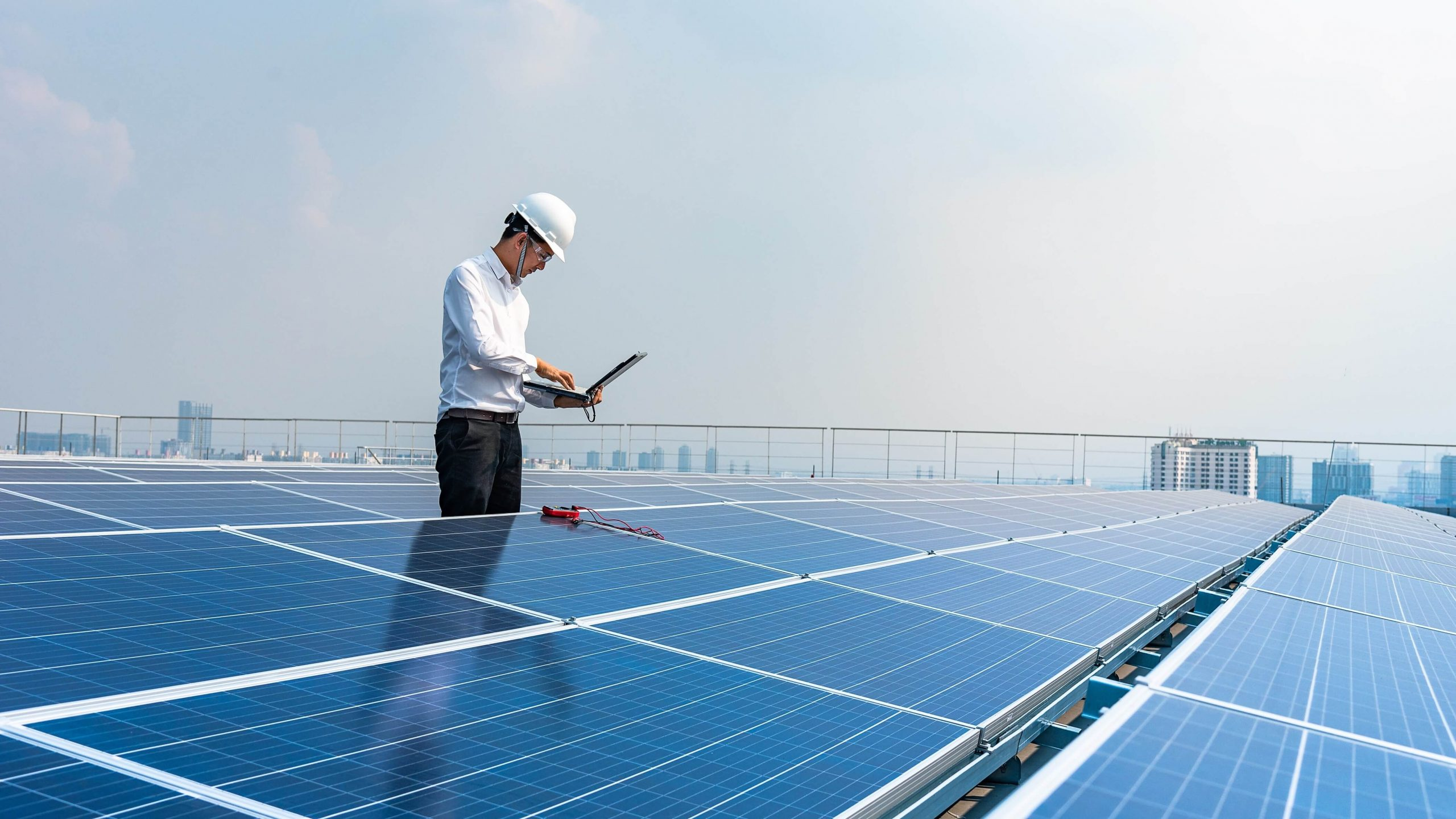 man on laptop on roof with solar panels