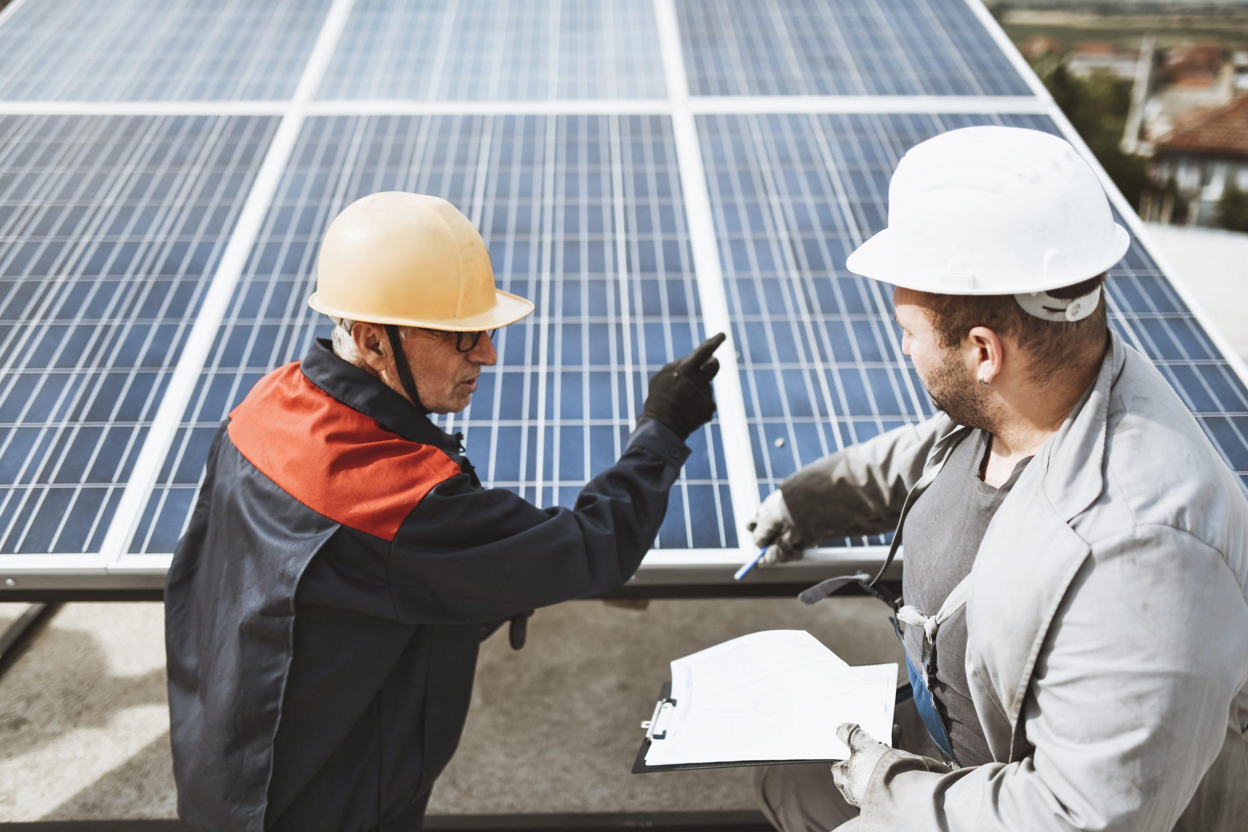 Men inspecting solar panels