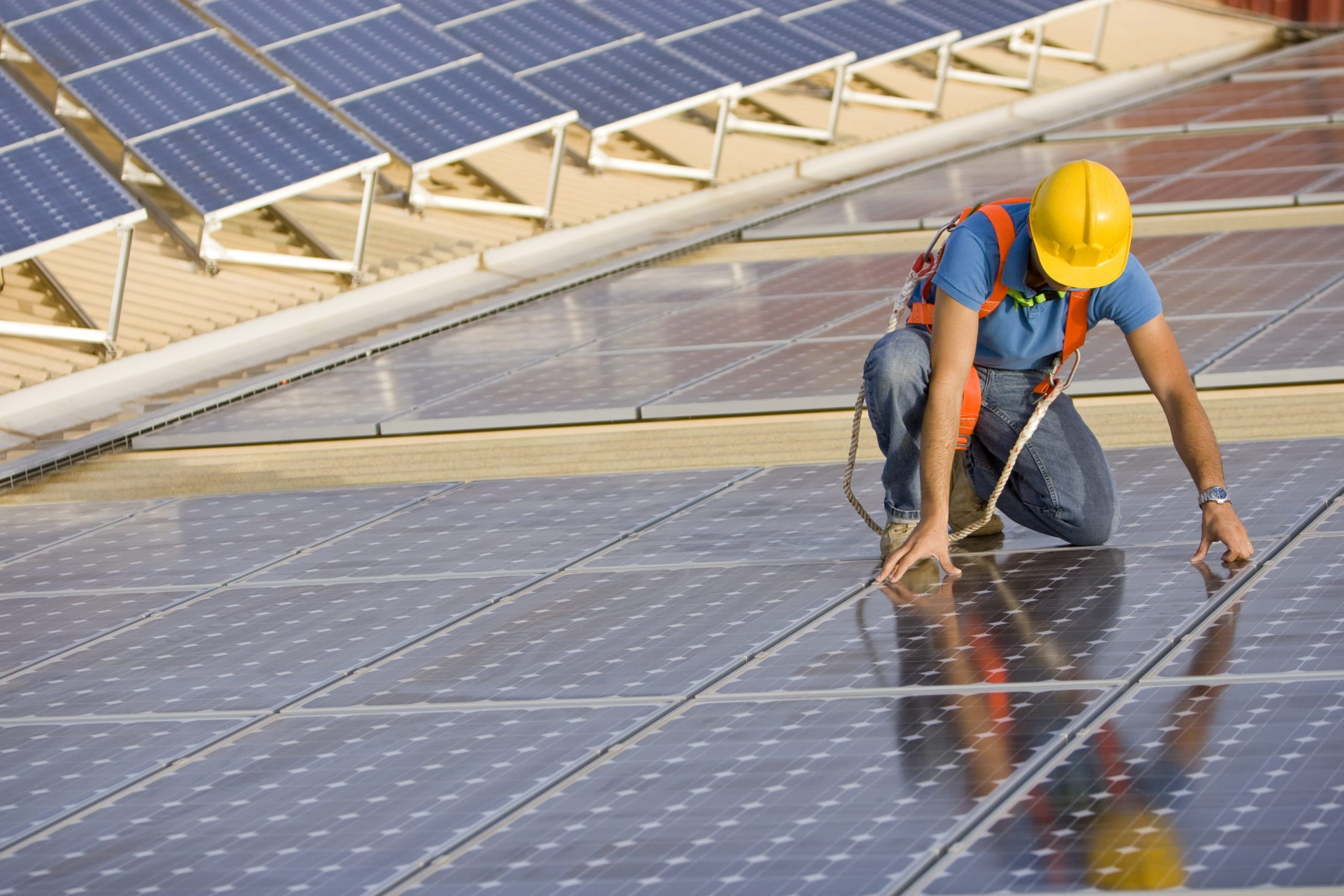 man in hardhat installing solar panels