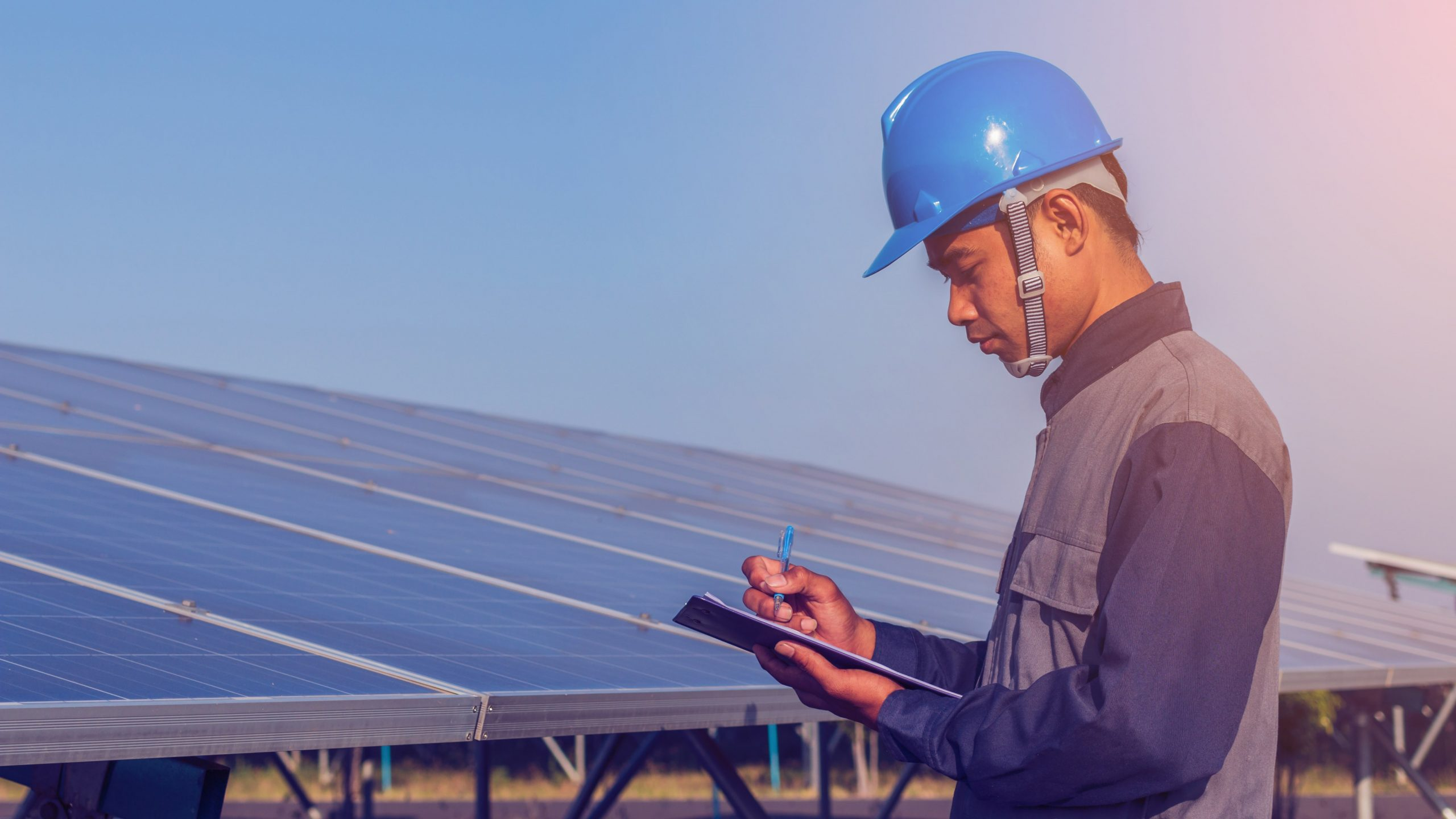 man reading from a clipboard in front of solar panels